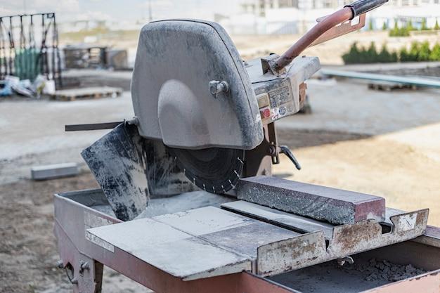 Die diamantkreissäge schneidet betonplatten. betonschneidemaschine nahaufnahme.