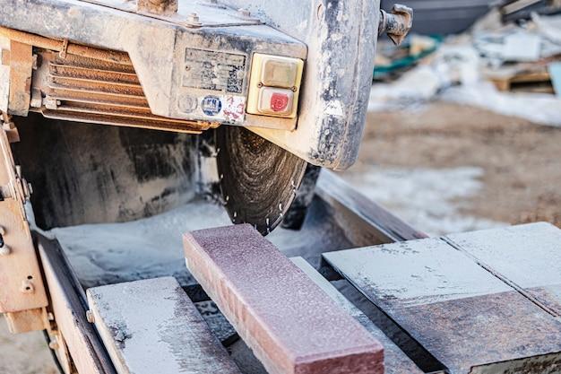 Die diamantkreissäge schneidet granit-gehwegfliesen. betonschneidemaschine nahaufnahme.