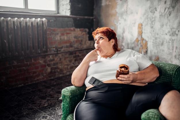 Die dicke frau sitzt auf einem stuhl und isst übergewichtige süßigkeiten. ungesunder lebensstil, fettleibigkeit