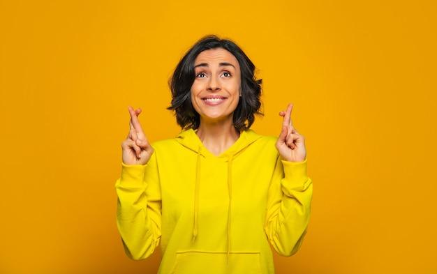 Die dinge laufen gut! aufgeregtes schönes mädchen in einem gelben kapuzenpulli, lächelnd und die daumen drückend