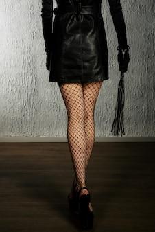 Die dominante frau in einem lederkleid mit einer peitsche in der hand zurück. bdsm-outfit