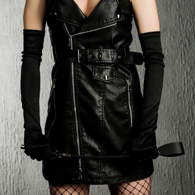 Die dominante frau in einem lederkleid mit einer tracht prügel in der hand. bdsm-outfit-bild