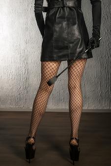 Die dominante frau in einem lederkleid mit einer tracht prügel in der hand zurück. bdsm-outfit