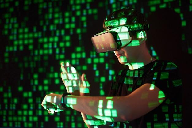 Die doppelbelichtung eines kaukasischen mannes und eines vr-headsets mit virtueller realität ist vermutlich ein spieler oder hacker, der den code in ein sicheres netzwerk oder einen server mit grünen codezeilen knackt