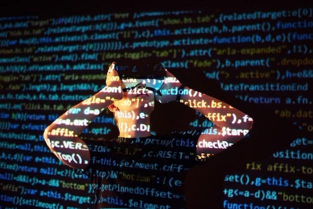 Die doppelte belichtung eines kaukasischen mannes und eines vr-headsets mit virtueller realität ist vermutlich ein spieler oder hacker, der den code in ein sicheres netzwerk oder einen sicheren server mit codezeilen knackt