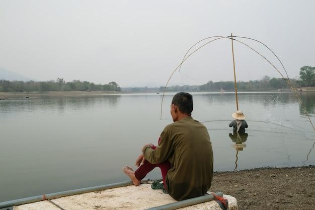 Die dorfbewohner fangen fische mit der fischfalle (netzfalle) im stausee