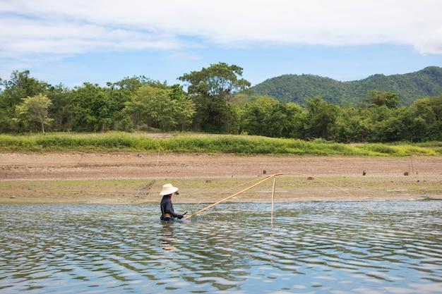 Die dorfbewohner suchen nach fischen in land mit trockenem und rissigem boden, weil die globale erwärmung trocken ist.