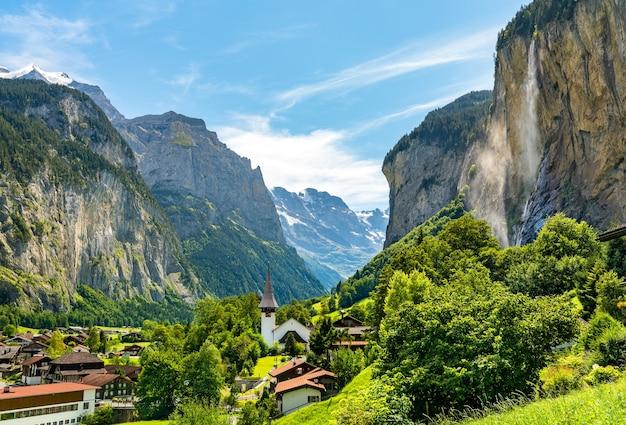 Die dorfkirche und die staubbachfälle in lauterbrunnen in der schweiz