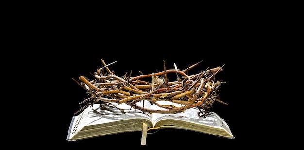 Die dornenkrone liegt im dunkeln auf dem buch der bibel. das konzept der karwoche und die kreuzigung jesu.
