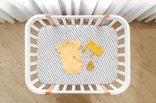 Die draufsicht auf babykleidung und zubehör im kinderbett, wiege. holzwiege für neugeborene im babyzimmer.