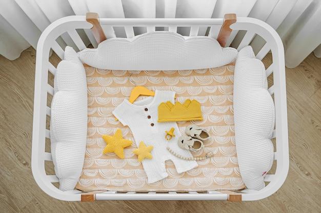 Die draufsicht auf babykleidung und zubehör im kinderbett, wiege. holzwiege für neugeborene mit weißen kissen im babyzimmer.