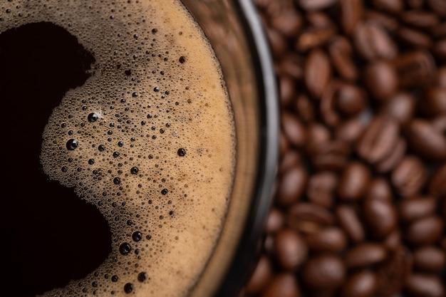 Die draufsicht auf eine kaffeetasse und eine gruppe schwarzer kaffeebohnen ist der hintergrund