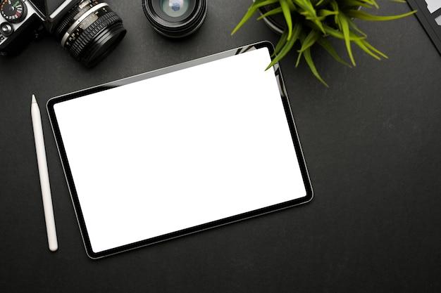 Die draufsicht auf einen dunklen kreativen arbeitsbereich mit einem digitalen tablet umfasst einen beschneidungspfad und eine kamera auf einem schwarzen tisch