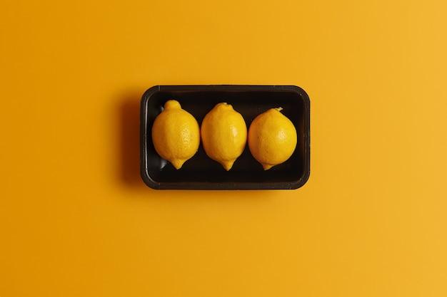Die draufsicht auf frische reife zitronen im behälter kann mit anderen mahlzeiten garniert werden, um einen sauren geschmack zu erzielen. hauptzutat für die herstellung von limonade. zitrusfrüchte mit vitaminen, mineralien und ätherischen ölen