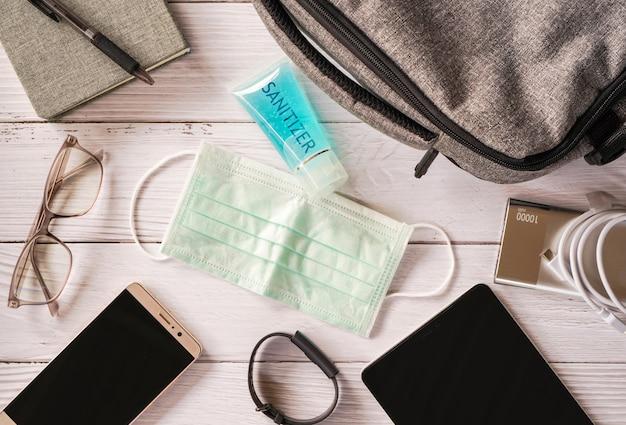 Die draufsicht auf persönliche gegenstände umfasst eine gesichtsmaske und ein handgel für desinfektionsmittel