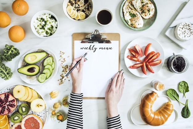 Die draufsicht auf superfood auf dem weißen marmortisch. flach liegen. verschiedene gemüsezutaten und gesundes essen für vegetarier. frühstückstisch. platz kopieren. vorlage.