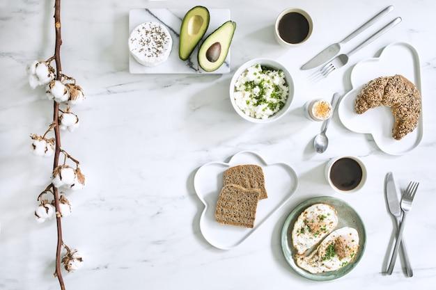 Die draufsicht auf superfood auf dem weißen marmortisch. flach liegen. verschiedene gemüsezutaten und gesundes essen für vegetarier. frühstückstisch.