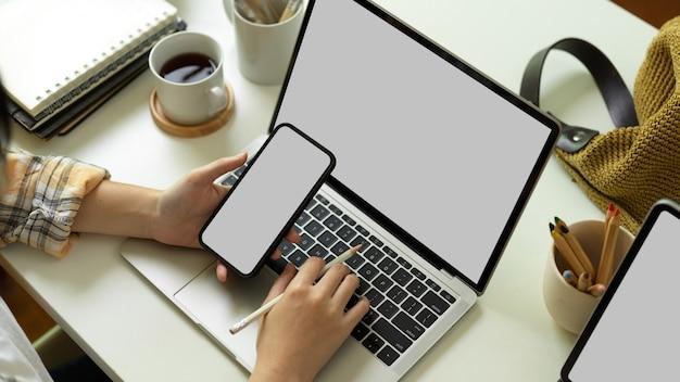 Die draufsicht der freiberuflerin in der scott-jacke, die an smartphone und laptop arbeitet, schließt beschneidungspfad auf home-office-schreibtisch ein