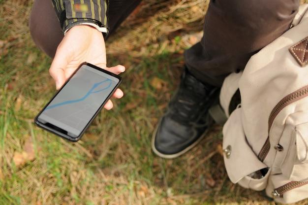 Die draufsicht des mannes sucht nach einem weg mit dem gps-navigator auf dem telefon allein in einem wald