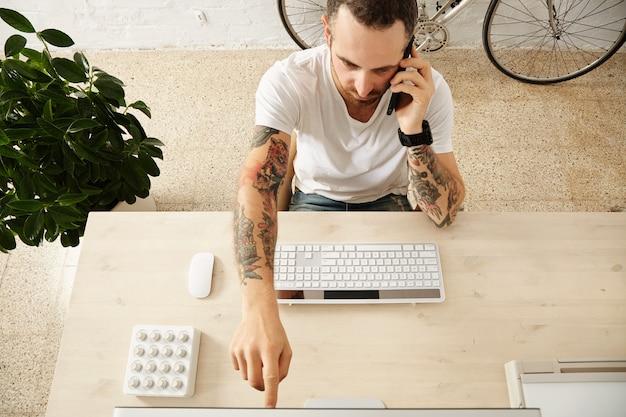 Die draufsicht des tätowierten mannes zeigt etwas auf dem display, während er auf seinem arbeitsdesktop im co-working-center telefoniert