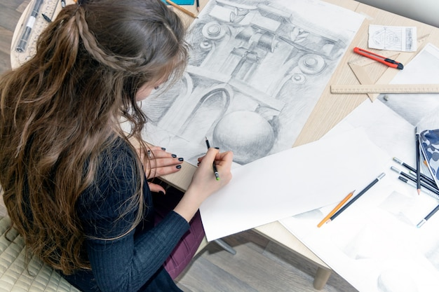 Die draufsicht des weiblichen architektendesigners zeichnet skizzen mit bleistift auf weißbuch. schwarzweiss-zeichnung eines architekturelements