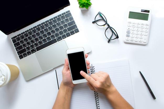 Die draufsicht von geschäftsleuten benutzt ein smartphone an einem weißen schreibtisch.