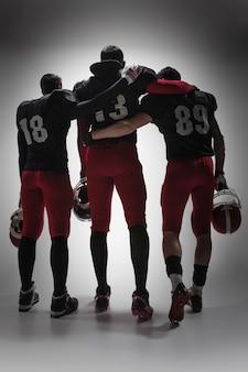 Die drei american-football-spieler auf grauem hintergrund