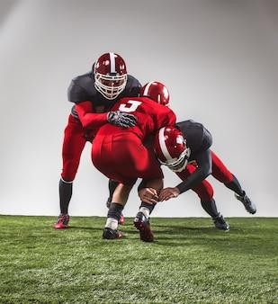 Die drei american-football-spieler in aktion auf grünem gras und grauem hintergrund.