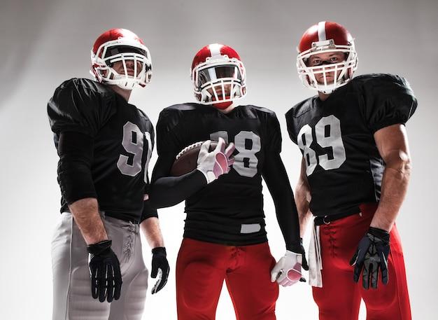 Die drei american-football-spieler posieren mit ball