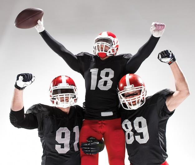Die drei american-football-spieler posieren