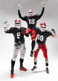 Die drei amerikanischen fußballspieler, die auf weißem hintergrund aufwerfen