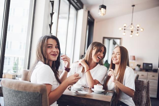 Die drei besten freundinnen versammelten sich, um kaffee zu trinken und zu klatschen. mädchen haben spaß und lachen