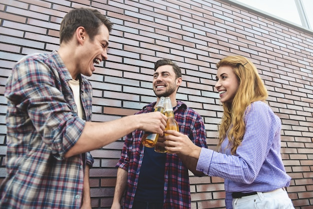 Die drei glücklichen freunde genießen mit bier auf einer braunen backsteinmaueroberfläche