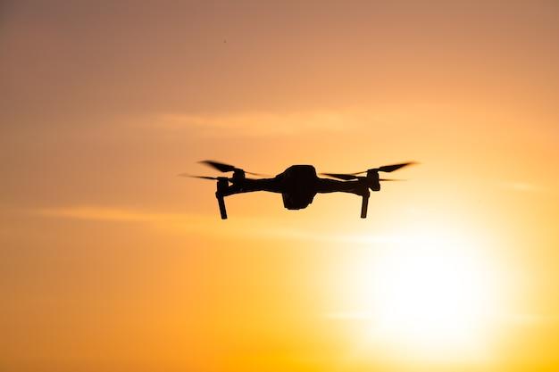 Die drohne ist bei sonnenuntergang im flug. videoaufnahmen von oben. ein artikel über die wahl eines quadrocopters. vor- und nachteile der drohne.