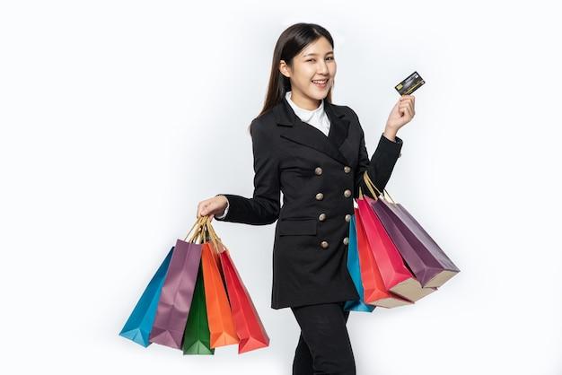 Die dunkel gekleidete frau ging einkaufen und trug kreditkarten und viele taschen