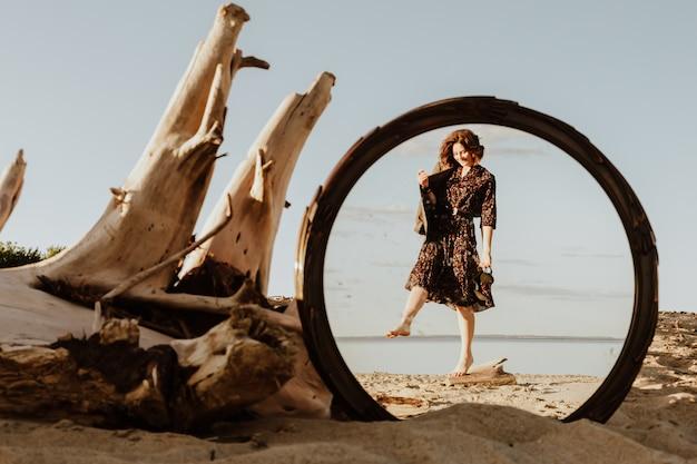 Die dunkelhaarige frau lächelt, geht am strand entlang und genießt an einem sommertag im spiegel die helle sonne.