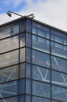 Die ecke des verglasten bürogebäudes mit der eingebauten modernen straßenlaterne