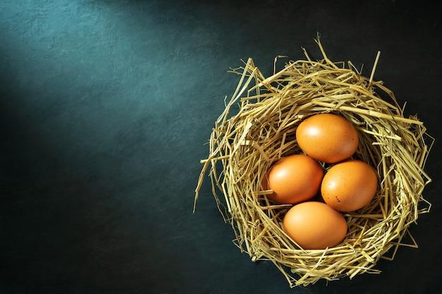 Die eier im nest gemacht vom reisstroh und vom morgensonnenlichthintergrund