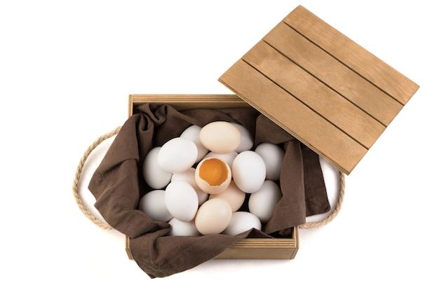 Die eier sind weiß und braun mit einem zerbrochenen ei in der mitte, in dem ein frisches eigelb sichtbar ist.