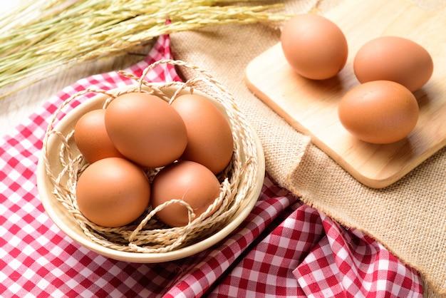Die eier werden in eine weiße schüssel gegeben und auf ein rotes schottisches plaid mit reisohr gelegt