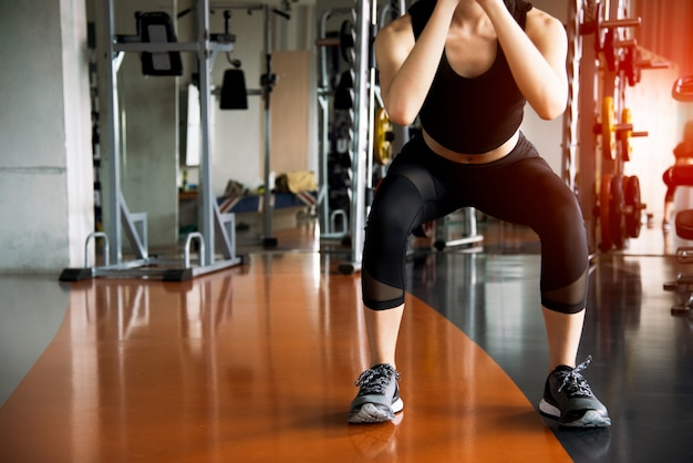 Die eignungsfrau, die hocketraining für fettes burning und beine tut, verstärken in der eignungssportturnhalle