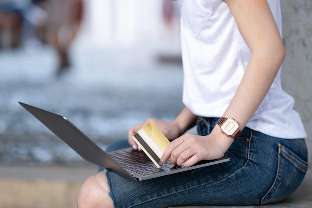 Die einkaufsmädchen, die kreditkarte halten, benutzen laptop.