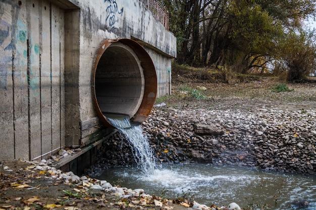Die einleitung von abwasser in den fluss durch ein großes rostiges rohr