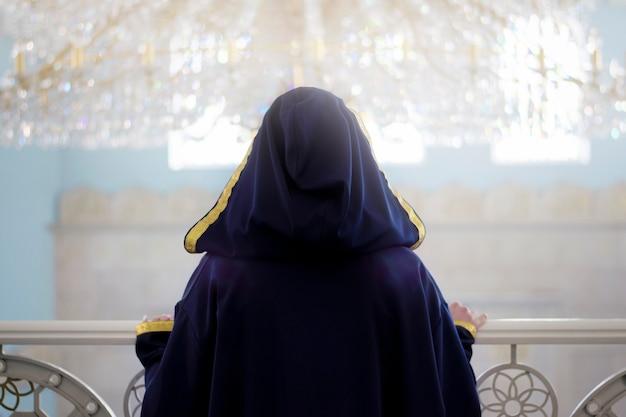 Die einsamkeit einer muslimischen frau in einer moschee.