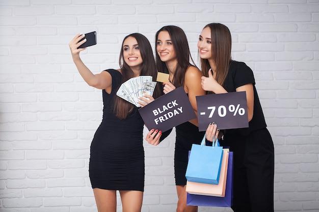 Die elegante brünette frau trägt ein schwarzes kleid mit einkaufstüten