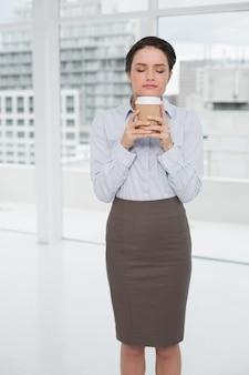 Die elegante geschäftsfrau, die kaffeegeruch mit den augen genießt, schloss im büro