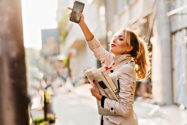 Die elegante geschäftsfrau im mantel erwischt ein taxi, das an einem sonnigen tag zur arbeit eilt