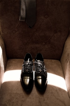 Die eleganten schuhe des bräutigams liegen auf einem weichen sessel