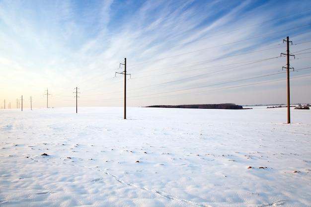Die elektrischen säulen durchquerten ein landwirtschaftliches feld. winter