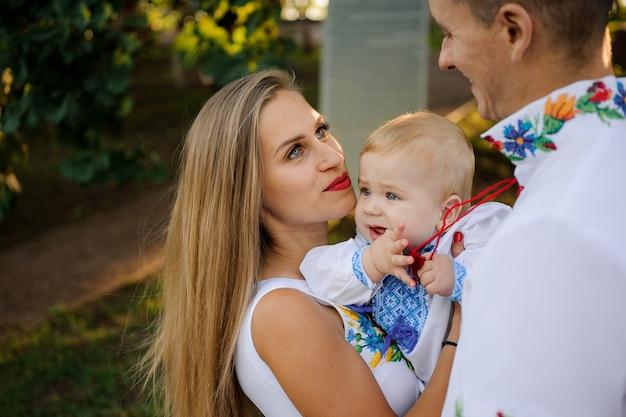 Die eltern, die an hände ein baby halten, kleideten im gestickten hemd an, das augen untersucht